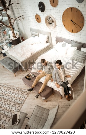 Necessary purchases. Joyful active couple checking softness of presented mattress while choosing good-quality furniture for bedroom #1299829420
