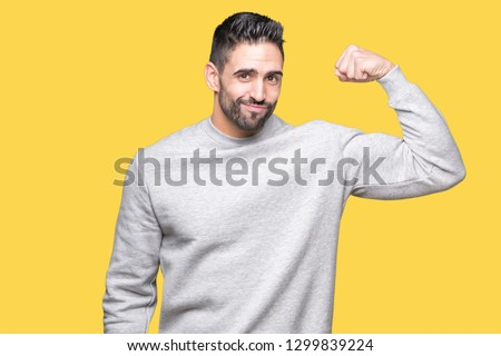 Young handsome man wearing sweatshirt over isolated background Strong person showing arm muscle, confident and proud of power #1299839224