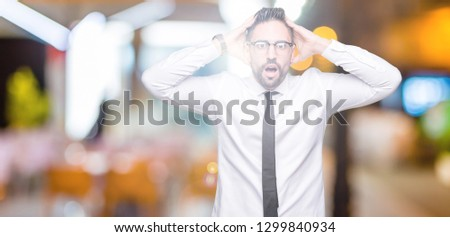 Young handsome business man wearing glasses over isolated background Crazy and scared with hands on head, afraid and surprised of shock with open mouth #1299840934