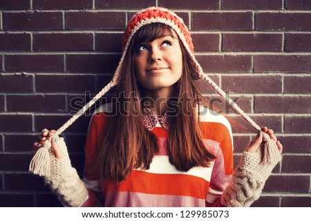 Portrait of young pretty funny smiling girl in cold weather dressed in color clothes and warm hat. Young happy woman having fun outdoor