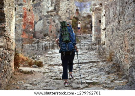 hiker woman walking by ruins of ancient city Kayakoy #1299962701