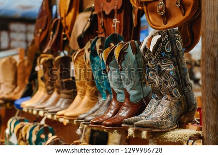 Stylish western boots with colorful embroidery on a shelf #1299986728