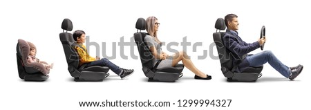 Full length profile shot of a father, mother, boy and baby in car seats with a fastened seat belt simulating a car ride isolated on white background #1299994327