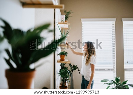 Woman with her Indoor Plants #1299995713