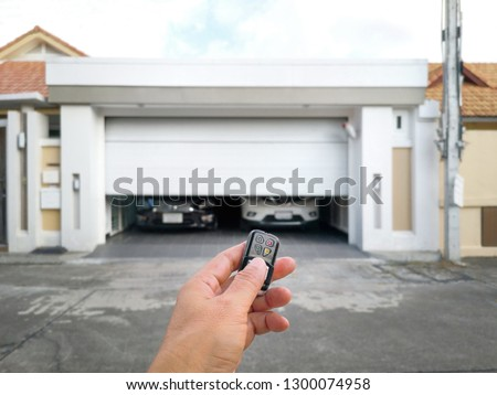 Hand holding the remote to open the sliding door.Remote control door.Electrical door.Automatic door. #1300074958