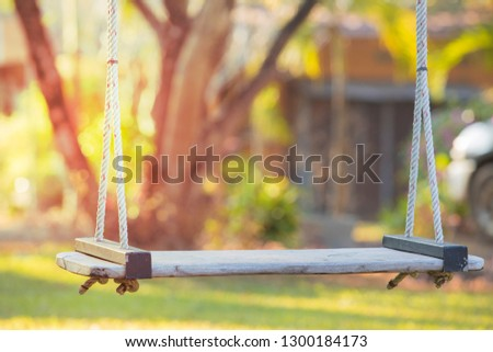 Empty swing on children playground,Children swing in the park,wooden swing,wooden swing on the lawn during the sunrise  #1300184173
