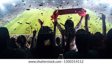 Fans celebrating the success of their favorite sports team on the stands of the professional stadium. Stadium is made in 3D. #1300314112