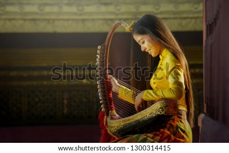 A beautiful woman in Mandalay, Myanmar came to dress up in the traditional style of Myanmar and play the artist pin-style music in Bagan #1300314415