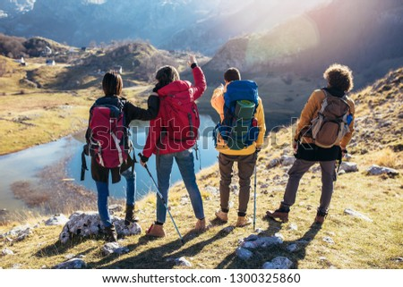 Group of hikers walking on a mountain at autumn day  #1300325860