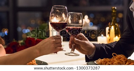 Hands holding glasses of wine on restaurant background. Let's have a toast concept #1300373287