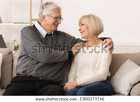 Loving senior couple relaxing and looking at each other on sofa at home #1300373746
