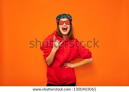 young and cool hipster girl having fun, with colored hat and sunglasses posing with good vibes to camera on orange background #1300403065