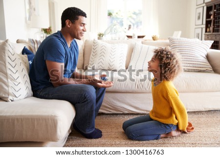 African American pre-teen girl kneeling in front of her dad to give him a present she has made, close up, side view #1300416763