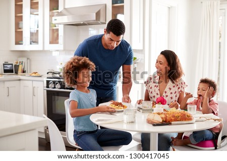 African American young mother sitting at table in the kitchen with children, father serving them food, selective focus #1300417045