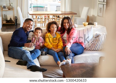 African American young grandparents sitting with their grandchildren on sofa in the living room watching TV, selective focus #1300420633