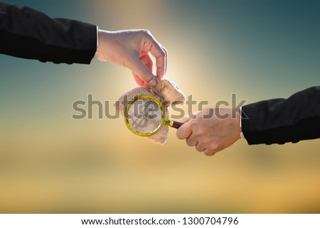 Investor hand hold a magnifier glass and money bag presenting to each other on photo blur cityscape background,  Loan and business investment of real estate in the future concept. #1300704796