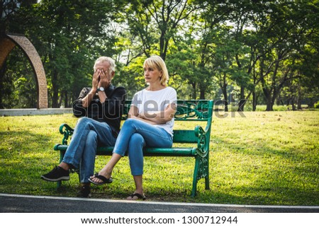 Depressed and sad old senior couple sitting on bench in the park background, Making decision of breaking up get divorced, Upset couple after fight dispute, #1300712944