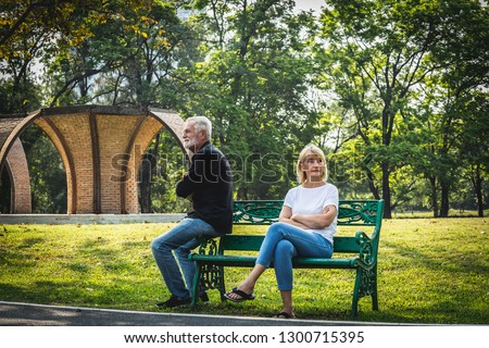 Depressed and sad old senior couple sitting on bench in the park background, Making decision of breaking up get divorced, Upset couple after fight dispute, #1300715395