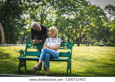 Depressed and sad old senior couple sitting on bench in the park background, Making decision of breaking up get divorced, Upset couple after fight dispute, #1300715401