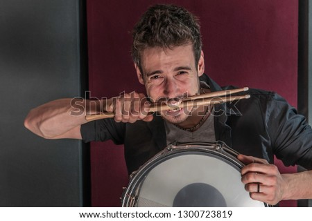 Young caucasian drummer with snare drum, biting his sticks #1300723819