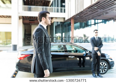 Executive protection agents standing by car while doing their duty in city #1300726771