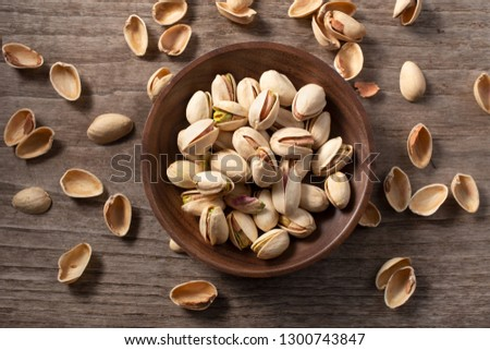 Top view of Pistachio in bowl with husks cracked on wooden table. Pistacia vera #1300743847