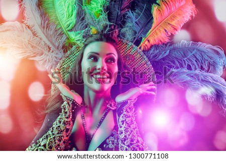 Beautiful young woman in carnival peacock costume. Beauty model woman at party over holiday background with magic glow. Christmas and New Year celebration. Glamour lady with perfect make up and #1300771108