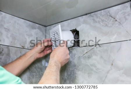 Man is installing the wall bathroom fan vent. Restoration process. #1300772785