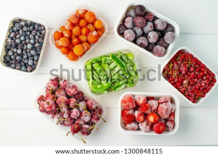Frozen berries and vegetables in plastic boxes on white wooden background. Royalty-Free Stock Photo #1300848115