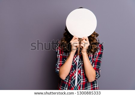 Close up portrait of unknown beautiful amazing she her lady arm show hold round card hide facial expression behind try guess my emotions wear casual checkered plaid shirt isolated grey background #1300885333