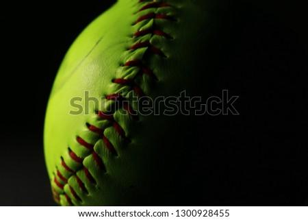 Bright softball on black background.