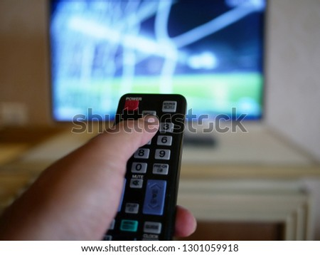 closeup of hand with the remote control television and presses the button. #1301059918