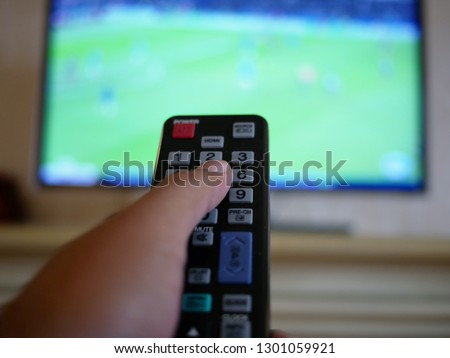 closeup of hand with the remote control television and presses the button. #1301059921
