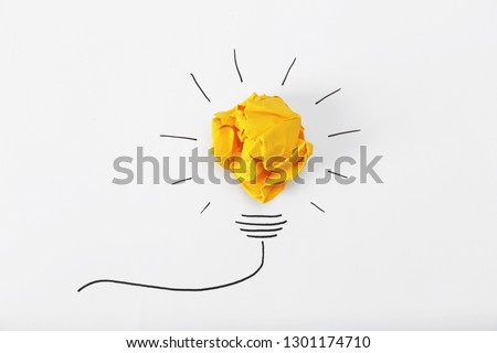 Composition with crumpled paper ball and drawing of lamp bulb on white background, top view. Creative concept #1301174710