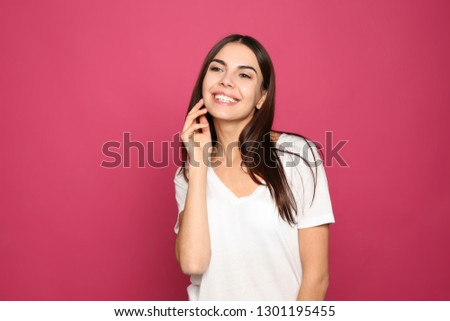 Portrait of young woman laughing on color background #1301195455
