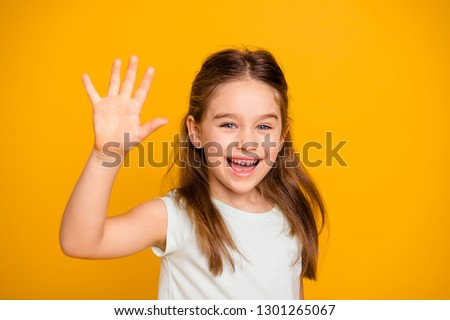Portrait of her she nice-looking cute attractive lovely pretty cheerful cheery positive pre-teen girl waving hi hello greetings I'm here isolated over bright vivid shine yellow background #1301265067