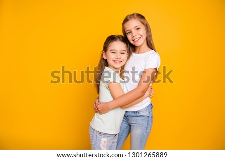Portrait of two nice-looking cute winsome sweet attractive lovely pretty cheerful cheery positive caucasian straight-haired girls cuddling isolated over bright vivid shine yellow background #1301265889