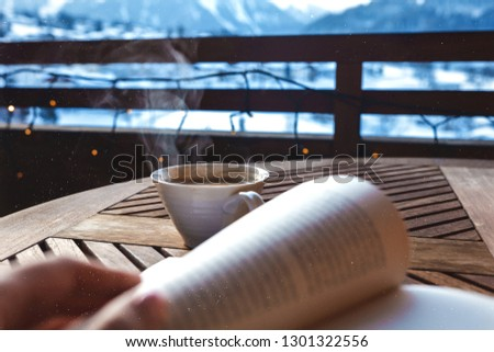 Picture of a cup of aromatic and tasty coffee, standing on the wooden table outdoor. Steam under the cup.Open book lying on the table.Amazing winter view on the Switzerland mountains covered with snow