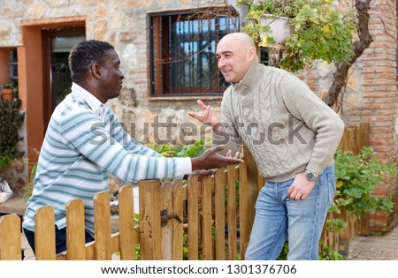 Two smiling male neighbors talking through wooden fence, discussing latest news #1301376706