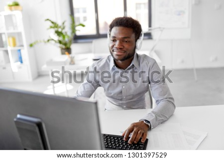 business, technology and people concept - happy african american businessman with headphones and computer listening to music at office #1301397529