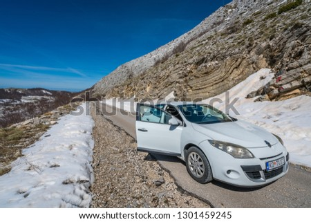 Lovcen National Park, Montenegro - April 2018 : White passenger car waiting for the road to be cleared of the small landslide in winter #1301459245