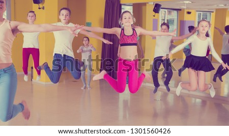 Group of sportive children with female teacher training in modern dance hall, jumping together #1301560426