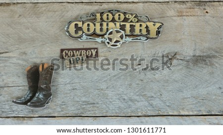 100% country sign next to cowboy boots on a wood background with writing space #1301611771