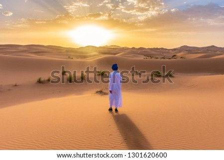 Berber man wearing traditional clothes in the Sahara Desert at dawn, Morocco #1301620600