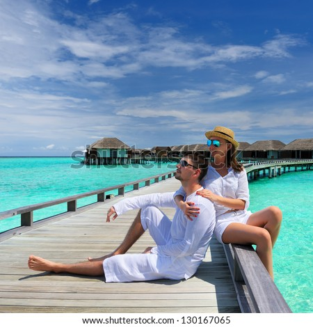 Couple on a tropical beach jetty at Maldives #130167065
