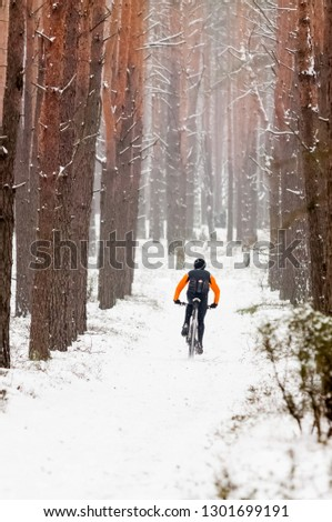 Winter riding a mountain bike in the forest #1301699191