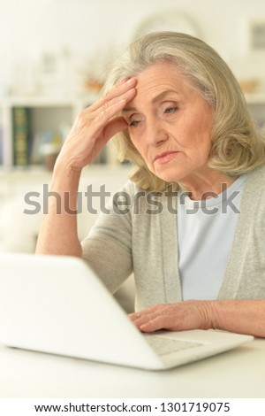 senior woman sitting at table with laptop #1301719075