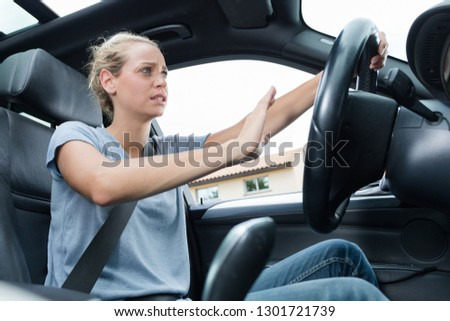 scared woman driving car in a panic #1301721739