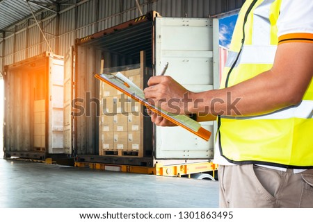 Freight and transportation Warehouse courier shipment. Warehouse staff holding  clipboard with control loading cargo shipment into a truck. #1301863495