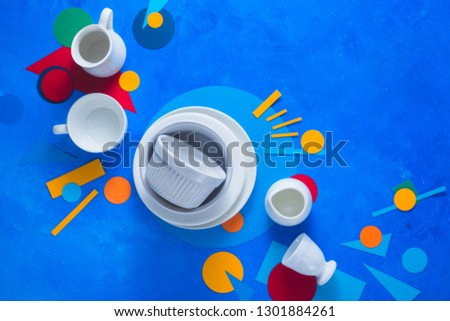 White dishes and cups on a colorful background with geometric shapes. Color block kitchenware flat lay with copy space. #1301884261